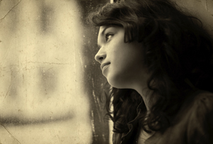 Beautiful girl looks out of the window. On its lips an easy smile, and behind a window a rain. Stylized as the old photos using the old paper.